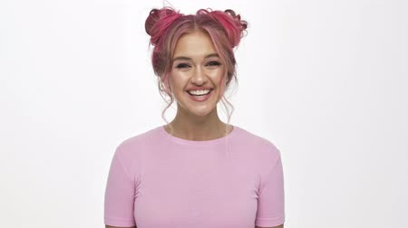 evet : A happy smiling young woman with the colored pink hairstyle is shaking her head agreeably isolated over white background