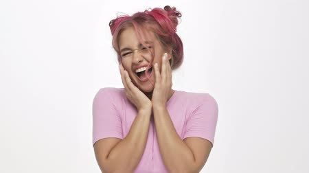 maravilhoso : A smiling young woman with the colored pink hairstyle is rejoicing isolated over white background