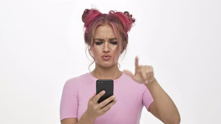 прическа : An attractive young woman with the colored pink hairstyle is using the smartphone over white background Стоковые видеозаписи