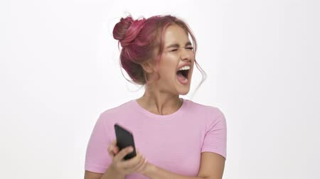puzzled : A displeased young woman with the color pink hairstyle is hiding her discontent while talking on the phone over white background