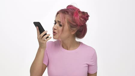 puzzled : A displeased angry young woman with the color pink hairstyle is quarreling while talking on the phone over white background