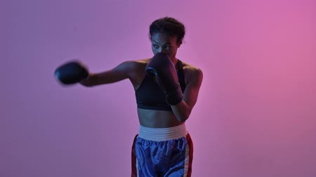 jimnastik : Side view of concentrated african sports woman boxer training in boxing gloves while looking away isolated led flashlights background Stok Video