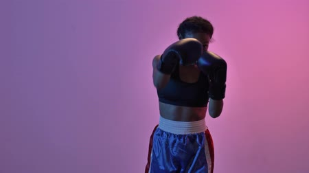 concentrato : Concentrated african sports woman boxer training in boxing gloves while looking at the camera isolated led flashlights background Filmati Stock