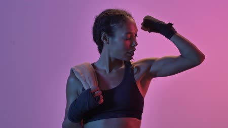 jimnastik : Happy african sports woman boxer standing with towel and showing her bicep isolated led flashlights background Stok Video