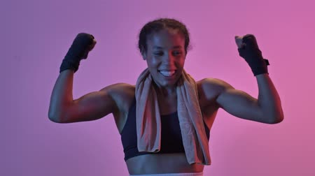 инструктор : Cheerful african sports woman boxer standing with towel and showing her biceps while looking at the camera isolated led flashlights background