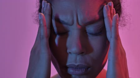 etnia africano : Close up view of confused african sports woman having headache and touching her temples isolated led flashlights background
