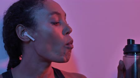 тренер : Close up view of pleased african sports woman in earphones listening music and drinking water from bottle while sitting near the wall isolated led flashlights background