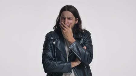 ひげを剃っていない : A stylish young man with long hair in a black leather jacket is yawning isolated over white background