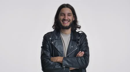 borotválatlan : A happy young man with long hair in a black leather jacket is smiling with crossing hands isolated over white background Stock mozgókép