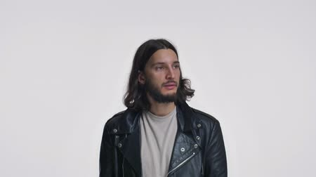 fascinante : A positive young man with long hair in a black leather jacket pushes the button and moving down like in the elevator isolated over white background