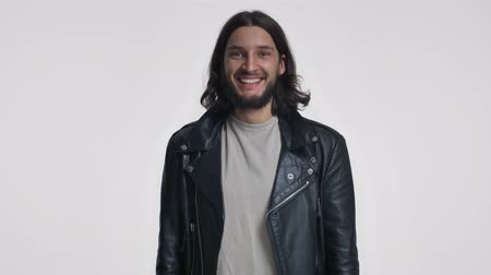 rejoice : A cheerful young man with long hair in a black leather jacket is laughing isolated over white background