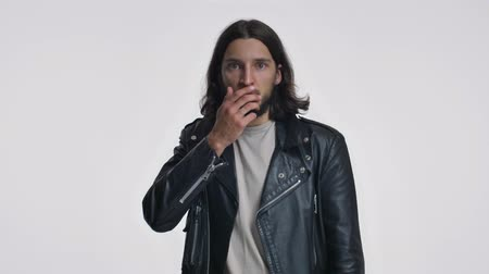 ひげを剃っていない : An attractive young man with long hair in a black leather jacket is becoming scared while covering his mouth isolated over white background 動画素材
