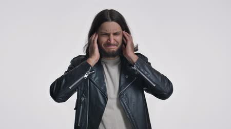 okładka : A displeased bored young man with long hair in a black leather jacket is covering his ears isolated over white background