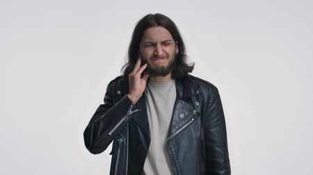 borotválatlan : A young man with long hair in a black leather jacket is touching his cheek, feeling toothache isolated over white background