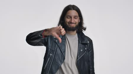 fascinante : A handsome young man with long hair in a black leather jacket is showing a thumb down gesture isolated over white background
