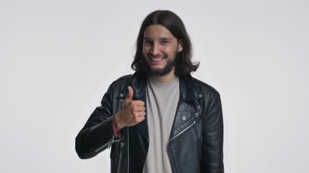 borotválatlan : A smiling young man with long hair in a black leather jacket is showing a thumb up gesture isolated over white background