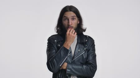 borotválatlan : A serious young man with long hair in black leather jacket is thinking about something then finds an idea isolated over white background