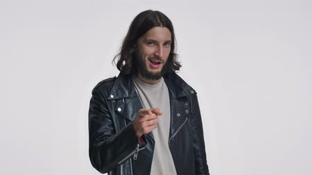 borotválatlan : A good looking young man with long hair in a black leather jacket is pointing to the camera isolated over white background Stock mozgókép