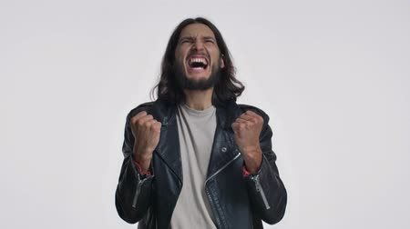 fascinante : A pleased young man with long hair in a black leather jacket is doing a winner gesture isolated over white background