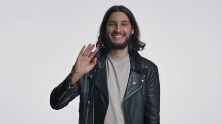 hóquei : A happy young man with long hair in a black leather jacket is waving his hand to the camera isolated over white background Stock Footage