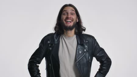 evet : An attractive young man with long hair in a black leather jacket is nodding his head positively isolated over white background Stok Video