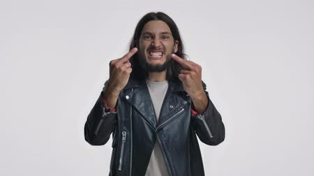 transação : An angry young man with long hair in a black leather jacket is showing a middle finger isolated over white background