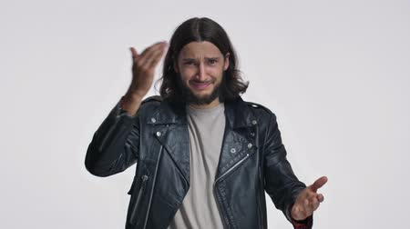 fascinante : A stunned young man with long hair in a black leather jacket is standing confused while shrugging shoulders isolated over white background Stock Footage