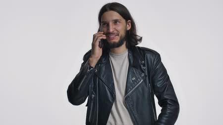 borotválatlan : A handsome young man with long hair in a black leather jacket is talking on the phone isolated over white background