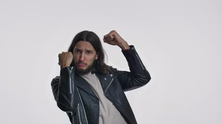 t shirt blanc : A confident young man with long hair in a black leather jacket is ready to fight isolated over white background