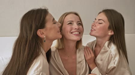 bachelorette party : Beautiful young girls are kissing on the bed at the hen party at home
