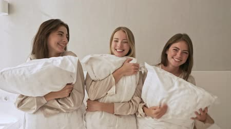 amigos : Beautiful young girls are hugging pillows on the bed at the light bedroom