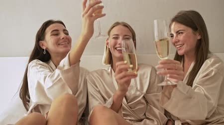 bachelorette party : Nice young girls friends are clink glasses while drinking champagne on the bed in the light bedroom