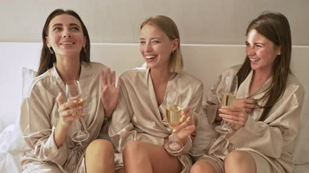 alkol : Happy young girls friends are drinking champagne on the bed in the light bedroom