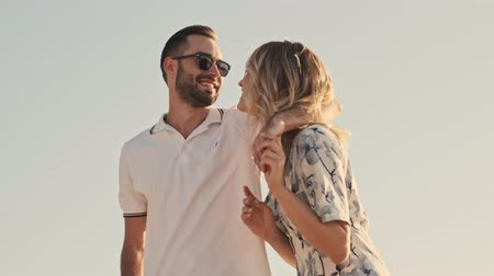 Bottom view of couple in casual clothes are hugging on the sunny beach Stock Footage
