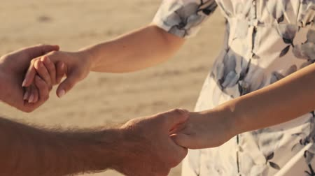 A close-up view of couples hands are holding each other on the sunny beach