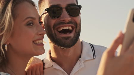 tarihleri : A close-up view of a smiling young couple in casual clothes is taking a selfie photo on the sunny beach