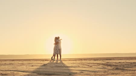 небритый : A beautiful romantic couple man and woman are hugging on the sunny beach near the lake against the sunrise