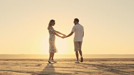 Back view of a lovely romantic couple in casual clothes is walking on the sunny beach near the lake Stock Footage
