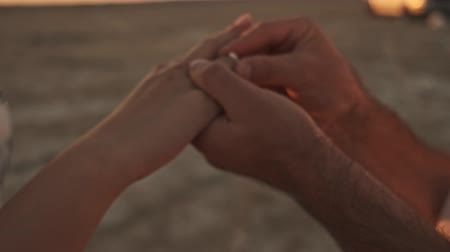 engaged : A cropped view of hands when the man is putting on a ring to a woman on the sunny beach near the lake Stock Footage