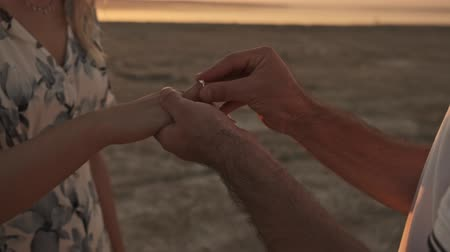 zasnoubený : A cropped view of hands when the man is putting on a ring to a woman while making a proposition of marriage on the sunny beach near the lake Dostupné videozáznamy
