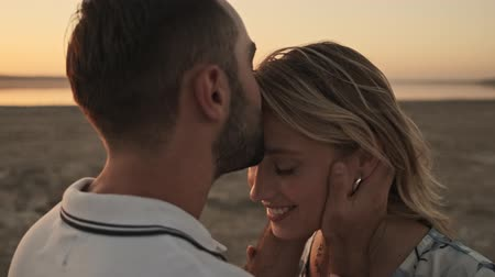 testa : A handsome man is kissing on the forehead a lovely girl on the sunny beach near the lake Stock Footage