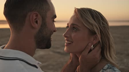 maravilhoso : A close-up view of a wonderful couple is looking at each other on the sunny beach near the lake Stock Footage