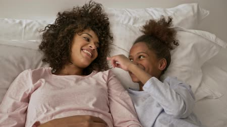 Top view of Cheerful african woman having fun with her little pretty daughter while lying on bed at home Stock Footage