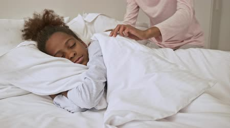 pajama : Pleased african woman covering her little sleeping pretty daughter with blanket in bed at home Stock Footage