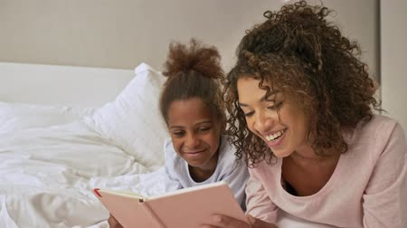 Cheerful african woman and her little pretty daughter reading book together while lying on bed at home Stock Footage