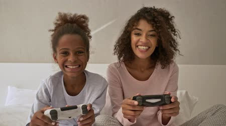 Joyful african woman and her happy little pretty daughter playing console together and having fun while sitting on bed at home