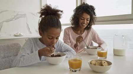 Joyful african woman and her happy little pretty daughter eating and enjoying this moment while sitting by the table on kitchen