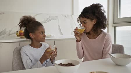 Satisfied african woman and her pleased little pretty daughter drinking juice and talking while sitting by the table on kitchen