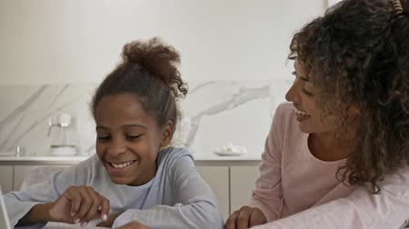 Satisfied african woman and her pleased little pretty daughter talking by videocall on laptop computer while sitting by the table on kitchen