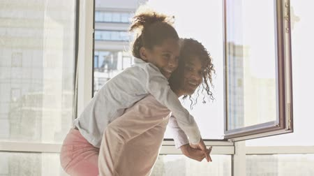 pajama : Happy african woman and her pleased little pretty daughter having fun together near the window at home Stock Footage